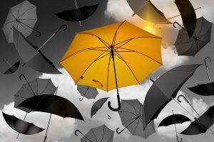 A yellow umbrella in a sky of grey umbrellas.