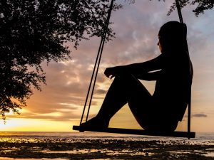 Woman sitting on swing at dusk