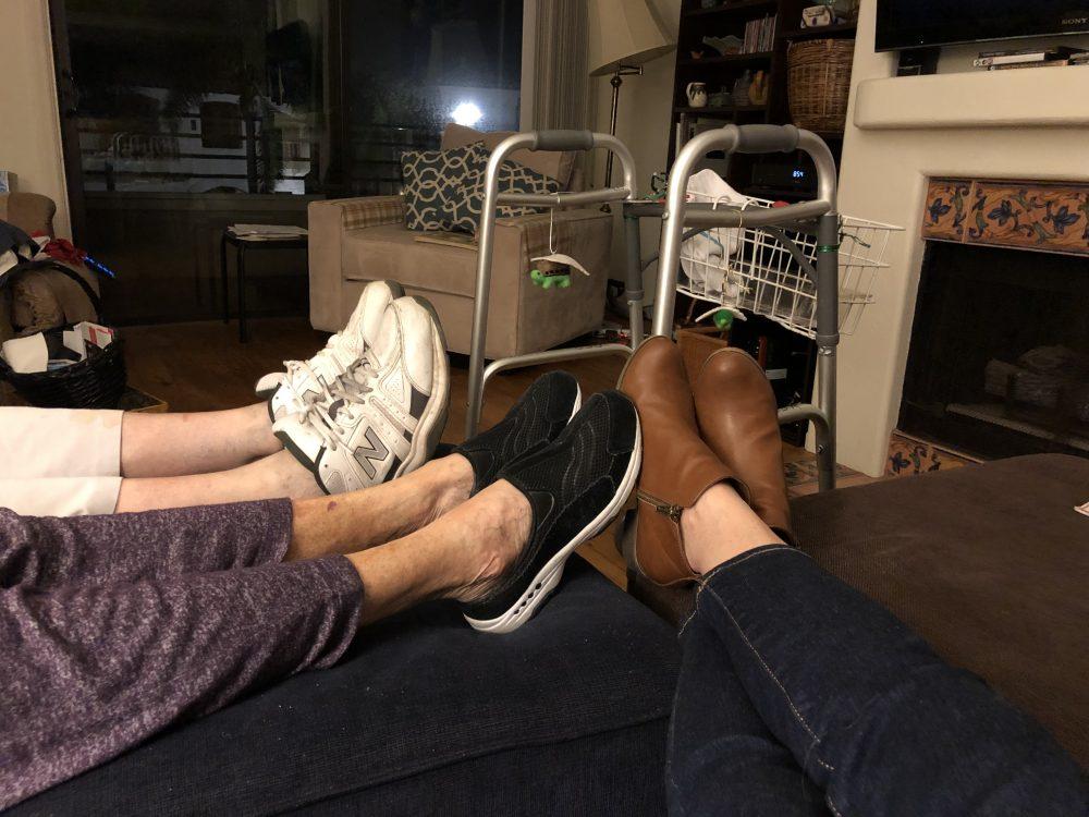 Three sets of feet resting on an ottoman.