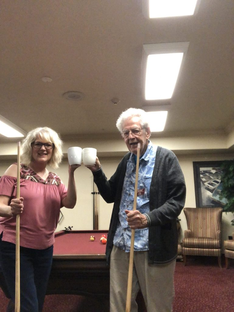Elderly man and blonde woman shoot pool.