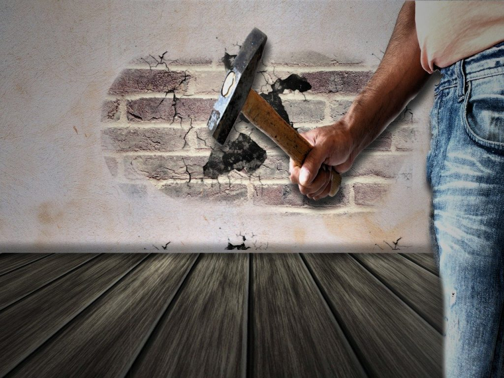 Man with sledge hammer about to smash a hole in a brick wall.