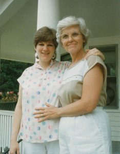 Gray-haired mother and pregnant daughter hugging and smiling on a house porch.