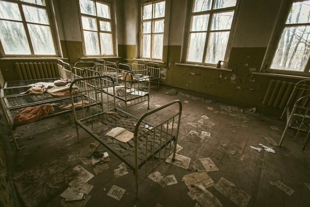 Abandoned room full of empty beds
